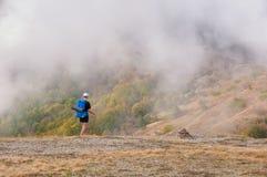 Equipaggi il viaggiatore con zaino e sacco a pelo che fa un'escursione in montagne di autunno che esaminano il bello paesaggio Immagini Stock