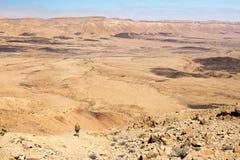 Equipaggi il viaggiatore con zaino e sacco a pelo turistico del tipo che sta guardante il pendio di montagna del deserto di vista Immagine Stock Libera da Diritti