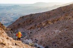 Equipaggi il viaggiatore con zaino e sacco a pelo turistico del tipo che sta guardante la montagna del deserto di vista Immagine Stock