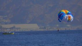 Equipaggi il volo su un paracadute speciale sopra il mare archivi video