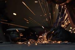 Equipaggi l'acciaio di taglio con una smerigliatrice di angolo producendo le scintille calde Immagini Stock