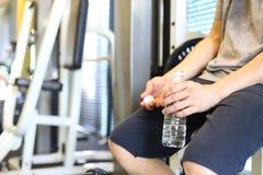 Equipaggi l'acqua di bottiglia della tenuta che ha una rottura dopo l'allenamento Immagine Stock