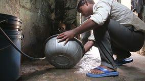 Equipaggi l'alimento di pulizia in acqua dal secchio sulla via di Jodhpur stock footage