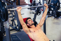 Equipaggi l'allenamento con il bilanciere sul banco alla palestra Fotografie Stock