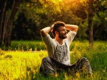 Equipaggi l'allungamento con le mani dietro la testa su erba al parco Fotografia Stock