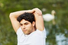 Equipaggi l'allungamento del suo braccio Fotografia Stock