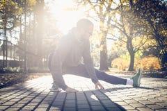 Equipaggi l'allungamento delle gambe prima dell'correre, stagione di autunno Fotografia Stock