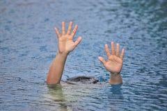 Equipaggi l'annegamento fuori nella piscina della porta mentre nuotano da solo, sollevando due mani e chiedendo l'aiuto SOS fotografie stock