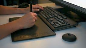 Equipaggi l'artista digitale che lavora con la compressa del disegno davanti al computer stock footage