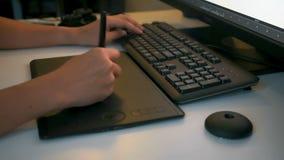 Equipaggi l'artista digitale che lavora con la compressa del disegno davanti al computer archivi video