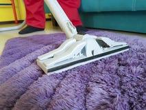 Equipaggi l'aspirazione il tappeto nella stanza che tiene il professionista immagine stock