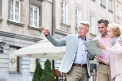 Equipaggi l'assistenza alle coppie di mezza età con il programma di strada in città immagini stock