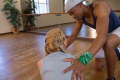 Equipaggi l'assistenza del ballerino femminile nell'allungamento sul pavimento Immagini Stock