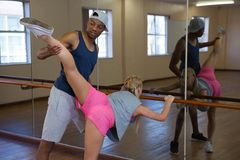 Equipaggi l'assistenza del ballerino nell'allungamento della gamba sulla sbarra Fotografie Stock Libere da Diritti