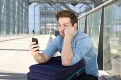 Equipaggi l'attesa all'aeroporto con l'espressione annoiata sul fronte Fotografia Stock