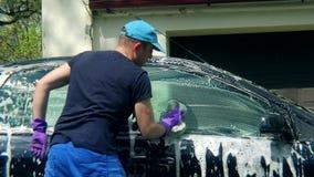 Equipaggi l'automobile di lavaggio del lavoratore con la spugna su un autolavaggio archivi video
