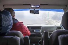 Equipaggi l'azionamento dalla strada stretta della montagna con nebbia pesante fotografia stock