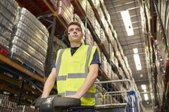 Equipaggi l'azionamento del trattore di rimorchio in un magazzino di distribuzione fotografie stock libere da diritti