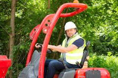 Equipaggi l'azionamento dell'escavatore Backhoe con il cappello bianco di sicurezza immagini stock