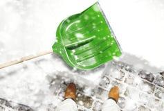 Equipaggi l'eliminazione della neve sul cortile con la pala durante le precipitazioni nevose Immagini Stock
