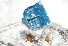 Equipaggi l'eliminazione della neve sul cortile con la pala durante le precipitazioni nevose Fotografia Stock