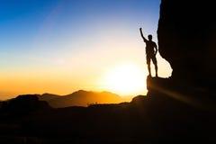 Equipaggi l'escursione del successo rampicante della siluetta nel tramonto delle montagne Immagine Stock Libera da Diritti