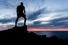 Equipaggi l'escursione della siluetta in montagne, in oceano e nel tramonto Fotografie Stock