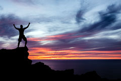 Equipaggi l'escursione della siluetta in montagne, in oceano e nel tramonto Fotografia Stock Libera da Diritti