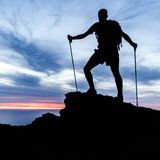 Equipaggi l'escursione della siluetta in montagne, in oceano e nel tramonto Immagini Stock