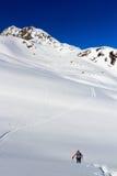 Equipaggi l'escursione sulle racchette da neve ed il panorama della neve della montagna con cielo blu nelle alpi di Stubai Immagine Stock