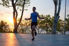 Equipaggi l'esercitazione con la salto-corda all'aperto durante il tramonto o l'alba nel mare, addestramento adatto del tipo dei  Immagini Stock Libere da Diritti