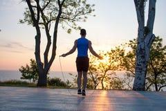 Equipaggi l'esercitazione con la salto-corda all'aperto durante il tramonto o l'alba nel mare, addestramento adatto del tipo dei  Fotografia Stock Libera da Diritti