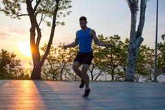 Equipaggi l'esercitazione con la salto-corda all'aperto durante il tramonto o l'alba nel mare, addestramento adatto del tipo dei  Fotografia Stock