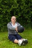 Equipaggi l'esercitazione con una palla medica da 3 chilogrammi su un prato verde Fotografia Stock