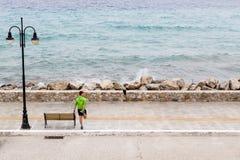 Equipaggi l'esercitazione e correre sulla via della città alla spiaggia Immagini Stock