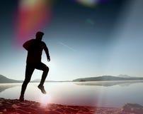 equipaggi l'esercitazione e l'allungamento sulla spiaggia del lago all'alba Stile di vita sano Giovane esercizio solo dell'uomo d Immagini Stock Libere da Diritti