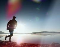 equipaggi l'esercitazione e l'allungamento sulla spiaggia del lago all'alba Stile di vita sano Giovane esercizio solo dell'uomo d Fotografia Stock Libera da Diritti