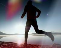 equipaggi l'esercitazione e l'allungamento sulla spiaggia del lago all'alba Stile di vita sano Giovane esercizio solo dell'uomo d Fotografie Stock Libere da Diritti