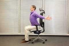 Equipaggi l'esercitazione sulla sedia in ufficio, stile di vita sano Fotografia Stock Libera da Diritti
