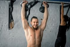 Equipaggi l'esercizio di sollevamento di allenamento di due kettlebell alla palestra Fotografia Stock Libera da Diritti