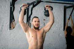Equipaggi l'esercizio di sollevamento di allenamento di due kettlebell alla palestra Immagini Stock