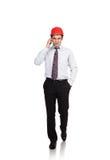Equipaggi l'ingegnere in un casco rosso che parla sul telefono immagine stock