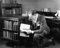 Equipaggi l'inginocchiamento nella sua biblioteca domestica che passa in rassegna un libro (tutte le persone rappresentate non so immagine stock libera da diritti