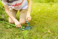 Equipaggi l'installazione del sistema di innaffiatura nel giardino sull'erba verde a del prato inglese fotografia stock