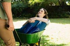 Equipaggi l'interazione con la donna mentre spingono la carriola in giardino Immagini Stock