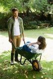 Equipaggi l'interazione con la donna mentre spingono la carriola in giardino Immagini Stock Libere da Diritti