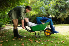 Equipaggi l'interazione con la donna mentre spingono la carriola in giardino Fotografia Stock