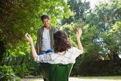 Equipaggi l'interazione con la donna mentre spingono la carriola in giardino Fotografie Stock Libere da Diritti
