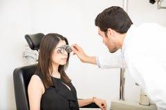 Equipaggi l'oculista che esamina la donna paziente con la prova franco dell'optometrista immagine stock