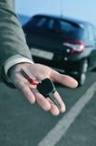 Equipaggi l'offerta della chiave dell'automobile all'osservatore Fotografia Stock